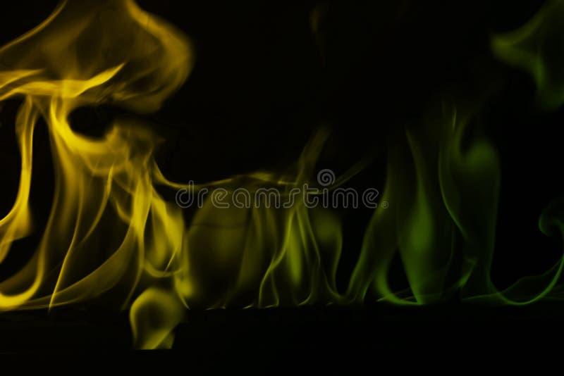 Abstraktes Grün und gelber Feuerrauch auf schwarzem Hintergrund, Feuerentwurf - Fotobild stockfotografie