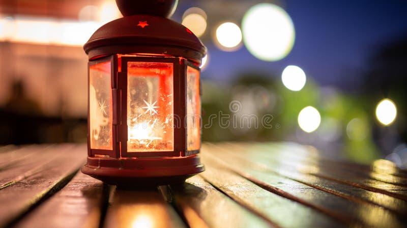 Abstraktes Kerzenlaternenlicht auf hölzerner Tabelle in Unschärfe bokeh Kneipe bezüglich stockbilder