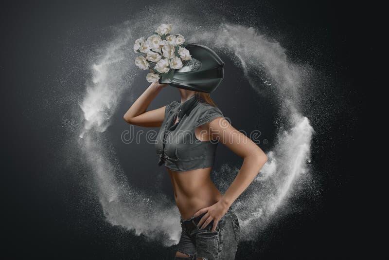 Abstraktes Modeporträt der jungen Frau im Motorradsturzhelm mit Blumen stockfoto
