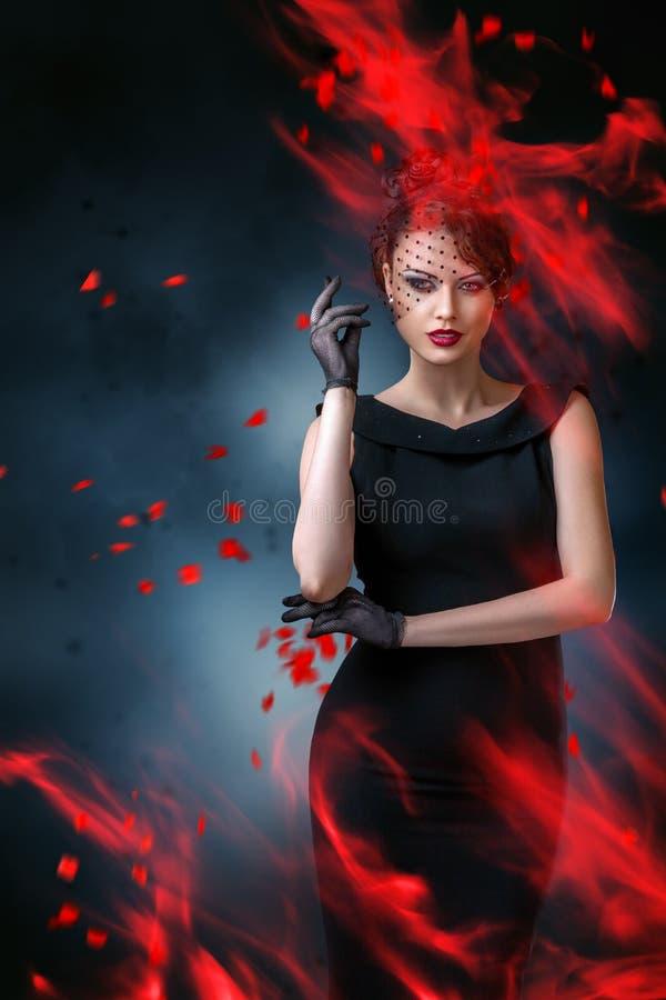 Abstraktes Modeporträt der jungen Frau mit Flamme stockbild