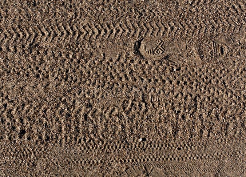 Abstraktes Muster von Fußdrucken und Fahrrad ermüden Bahnen auf Sand lizenzfreies stockbild