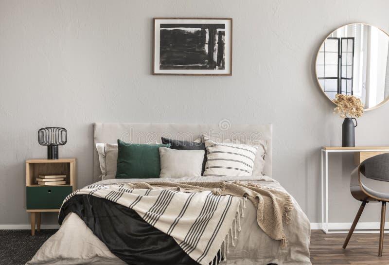 Abstraktes schwarzes Ölgemälde im Rahmen auf leerer beige Wand des gemütlichen Schlafzimmers lizenzfreies stockbild