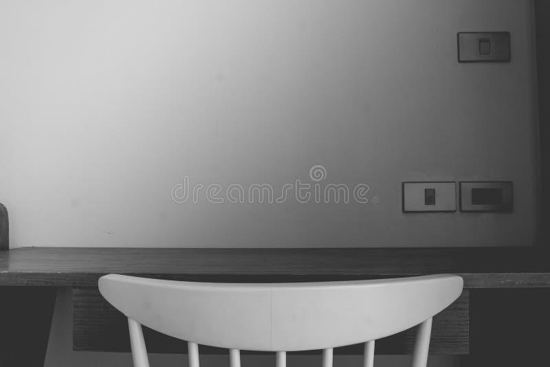 Abstraktes Schwarzweiss-Bild des leeren Holztischs und des Stuhls mit weißer Wand im Hintergrund lizenzfreie stockfotos