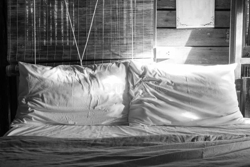 Abstraktes Schwarzweiss-Weiß des Bildes zwei zerknitterte Kissen auf Bett mit dem Sonnenlicht, das von der rechten Hand des Schla lizenzfreie stockfotos