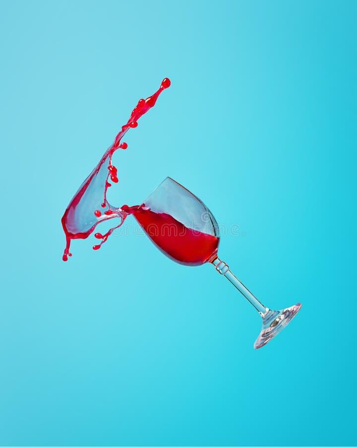 Abstraktes Spritzen des Rotweins in einem Glas auf einem blauen Hintergrundabschluß oben stockfoto