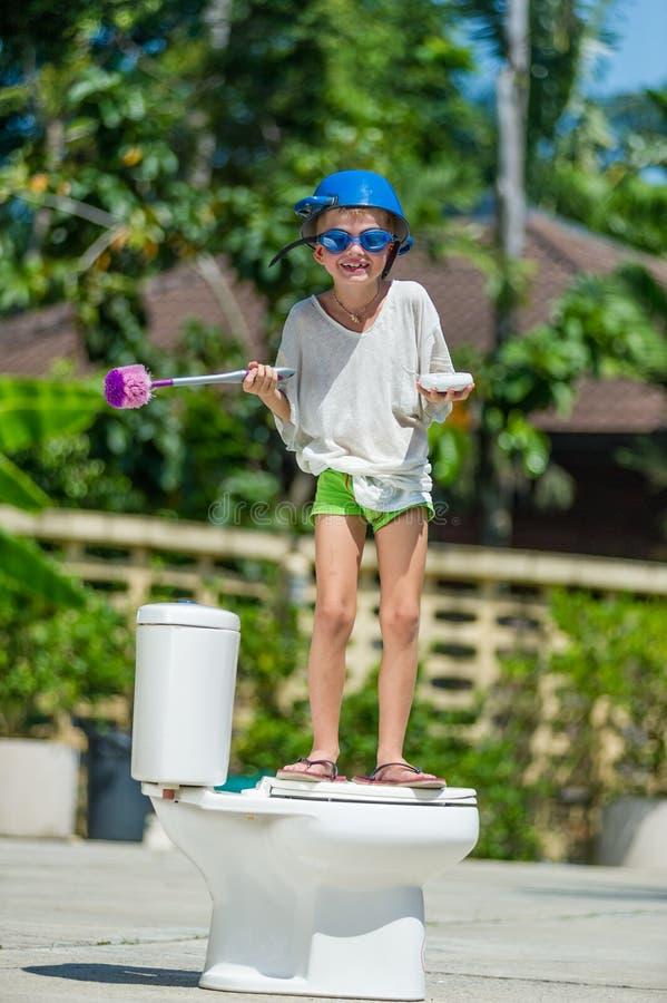 Absurd beeld: het leuke jongen dansen op het toilet, dat is installeert royalty-vrije stock foto