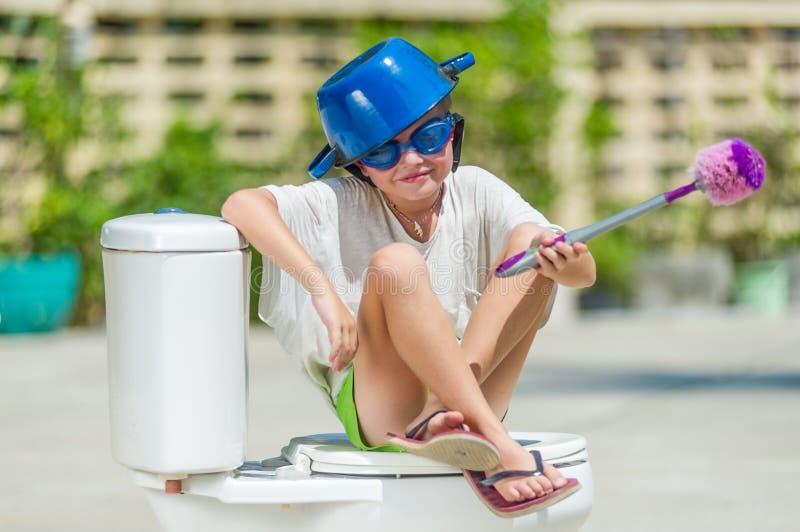 Absurd beeld: leuke jongen die in beschermende brillen op het toilet zitten, dat royalty-vrije stock foto's