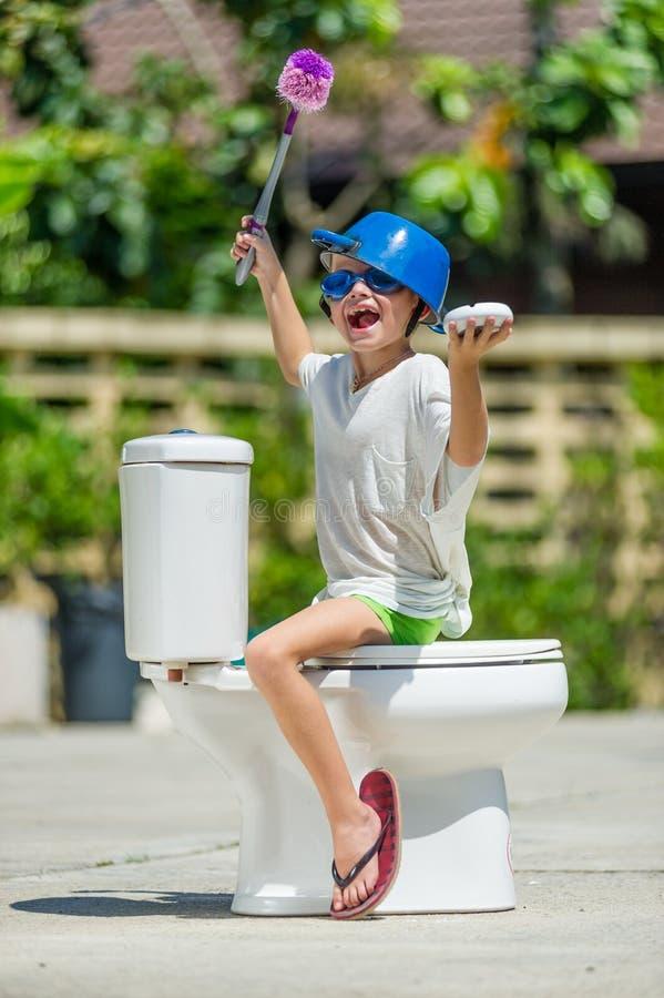 Absurd beeld: leuke jongen die op het toilet dansen, dat in het midden van de straat geïnstalleerd is Pan op zijn hoofd stock fotografie