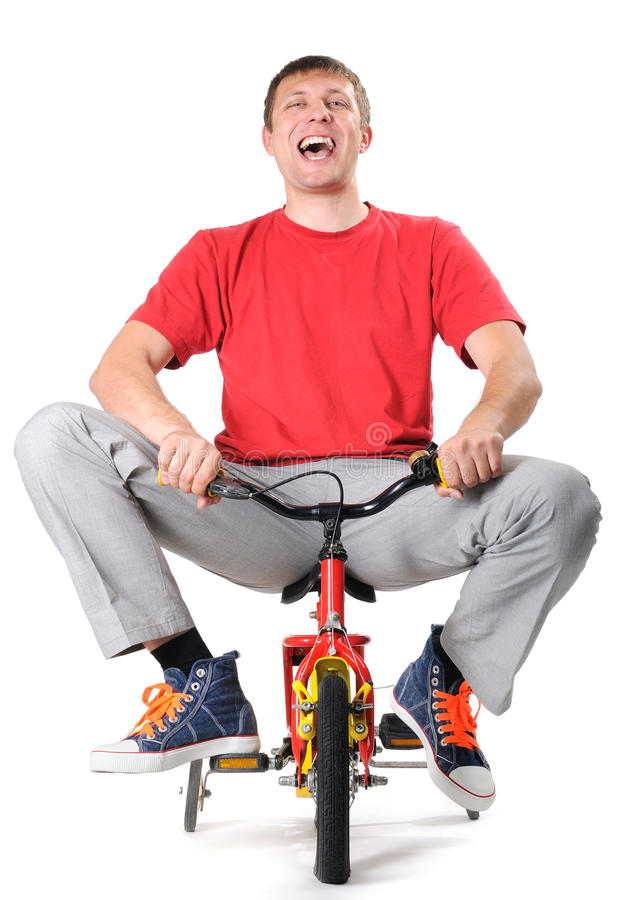 Absurd male on a children's bicycle. (withe background royalty free stock photo
