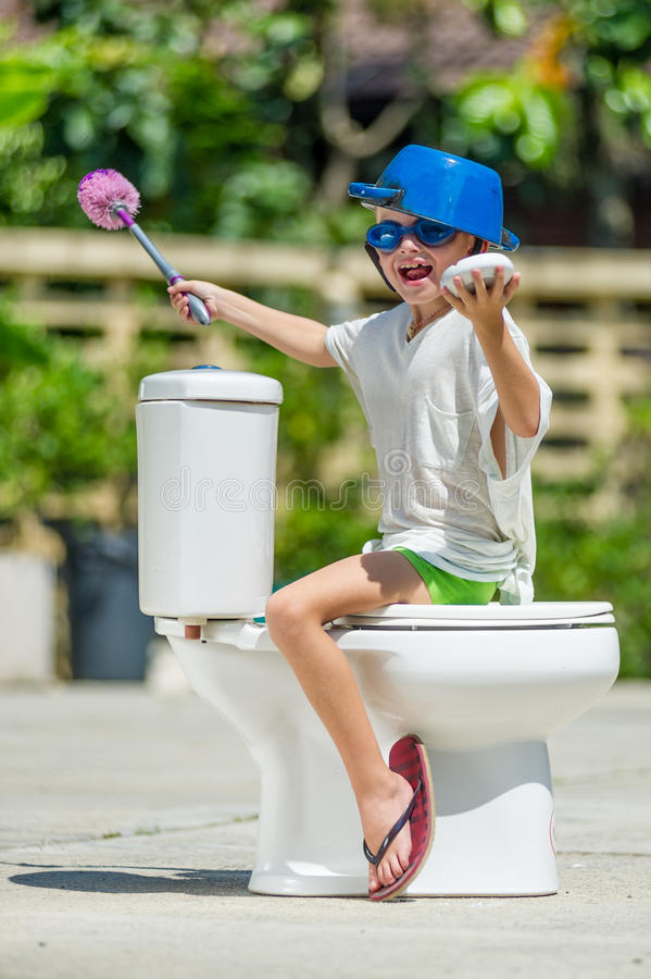 Absurd picture - astride a toilet: cute boy in goggles sitting o. Absurd picture: cute boy dancing on the toilet, which is installed in the middle of the street stock photos