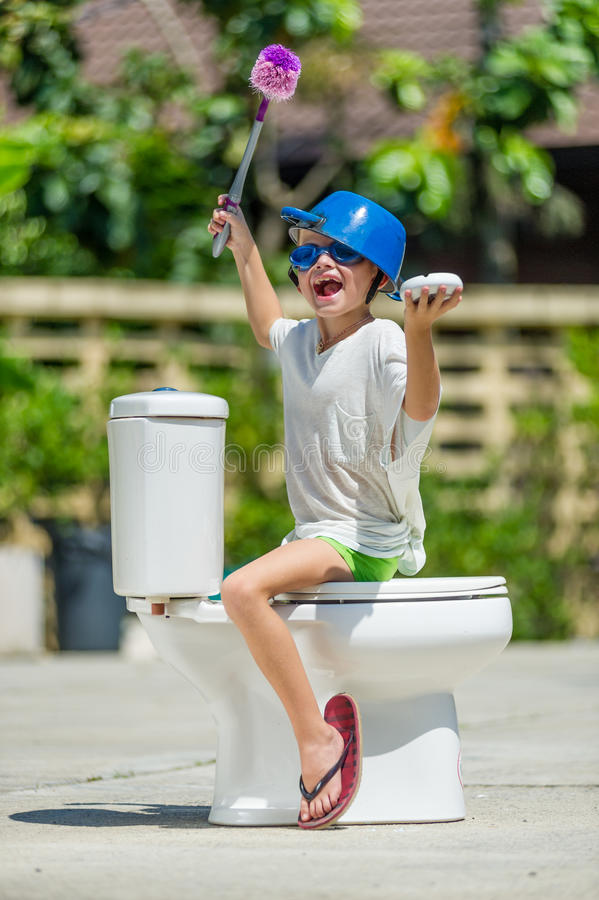 Absurd picture: cute boy dancing on the toilet, which is installed in the middle of the street. Pan on his head.  stock photography