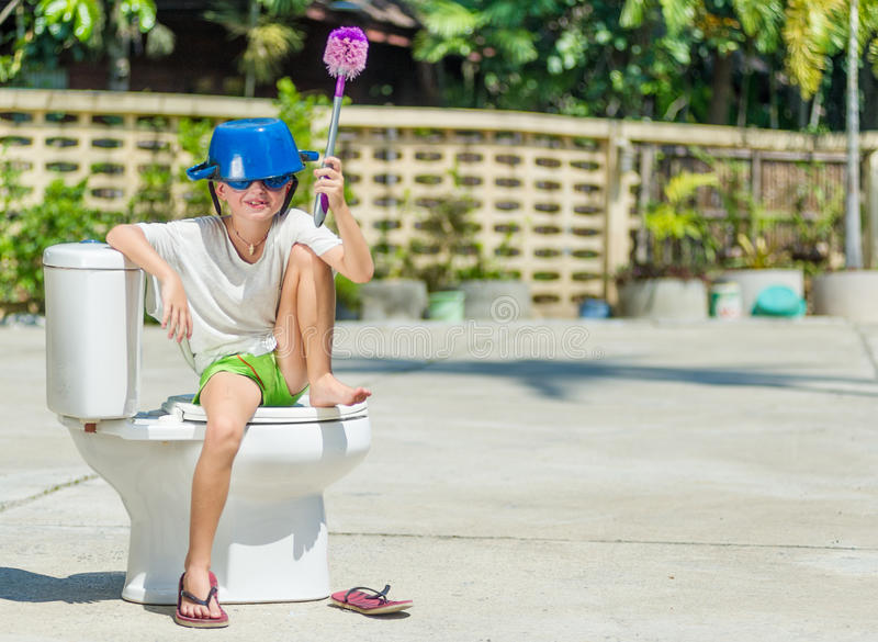 Absurd picture: cute boy in goggles sitting on the toilet, which. Absurd picture: cute boy dancing on the toilet, which is installed in the middle of the street royalty free stock images