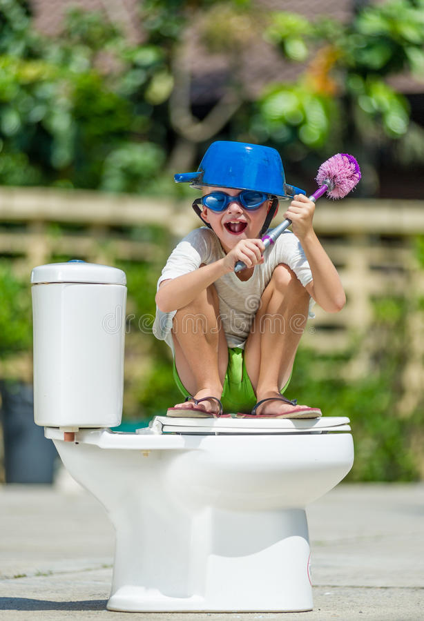 Absurd picture: cute boy in goggles sitting on the toilet, which. Absurd picture: cute boy dancing on the toilet, which is installed in the middle of the street stock photography