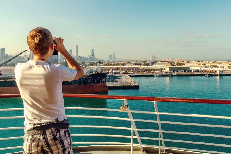 Abu Dhabi, Arabische Emirate - 13. Dezember 2018: Junger Mann, der durch Ferngläser von einem Kreuzfahrtschiff zu einer Stadt auf stockbild