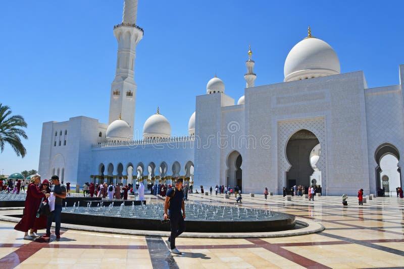 Abu Dhabi F?renade Arabemiraten, mars, 19, 2019 Folk som g?r n?ra Sheikh Zayed Grand Mosque i Abu Dhabi, F?renade Arabemiraten royaltyfri bild