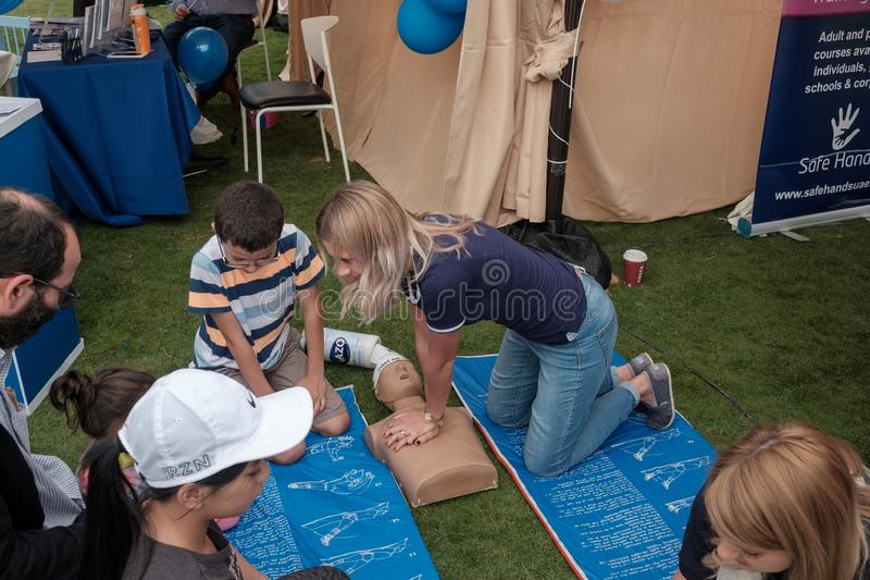 Abu Dhabi, UAE: Junger weiblicher Ersthelfer, der CPR zu den Kindern mit blindem Kind zeigt stockfotografie