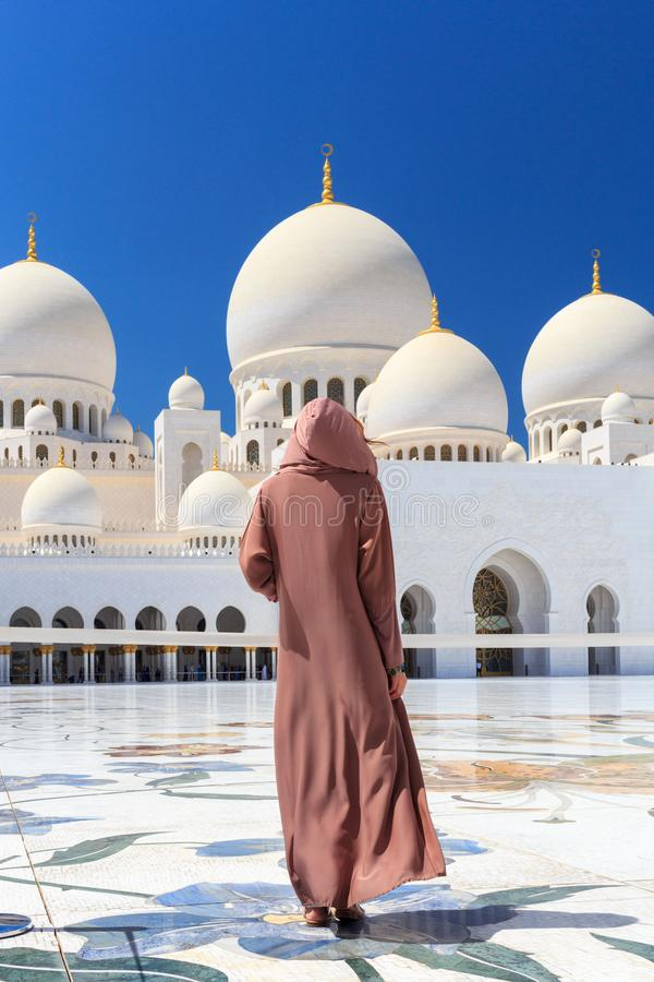ABU DHABI UAE - MARS 11 2019: Kvinna med den traditionella kl?nningen av brun f?rg inom Sheikh Zayed Mosque Abu Dhabi som f?renas royaltyfri bild