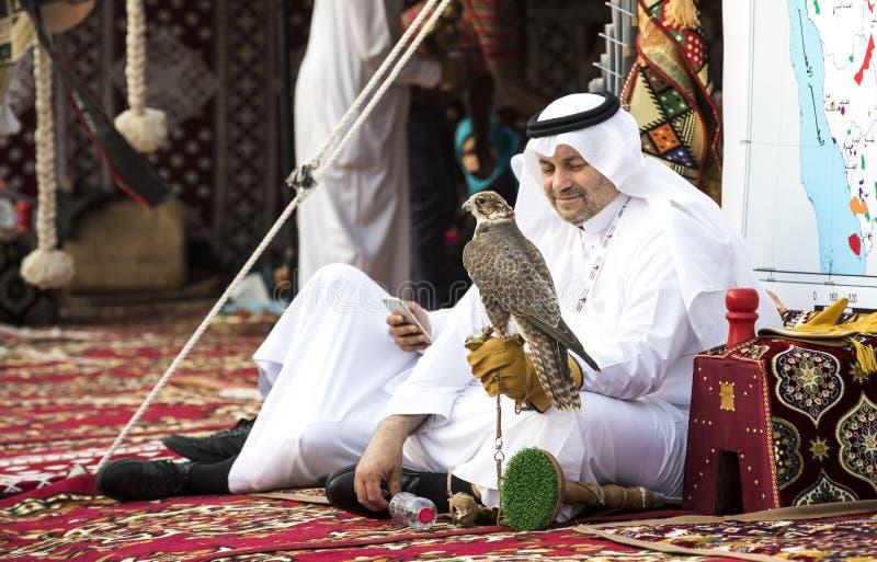 Emirati man with a falcon. Abu Dhabi, United Arab Emirates, December 8th, 2017: emirati man with his falcon at a Falconry festival stock image