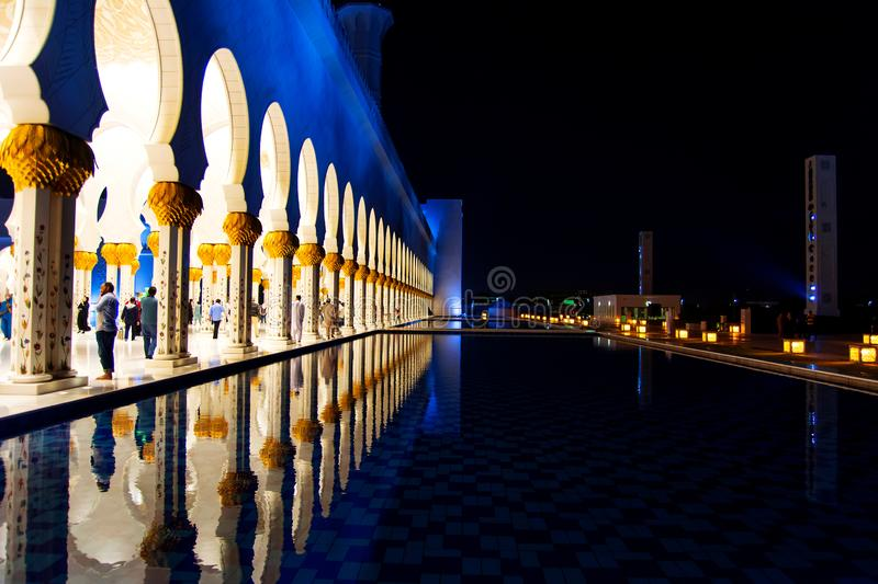 Abu Dhabi, United Arab Emirates - January 26, 2018: Crowded Sheikh Zayed Grand Mosque interior reflected in the surface at night royalty free stock photos