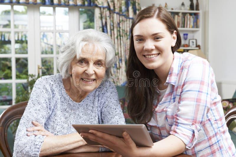 A abuela adolescente de la nieta mostrando cómo utilizar la etiqueta de Digitaces foto de archivo libre de regalías