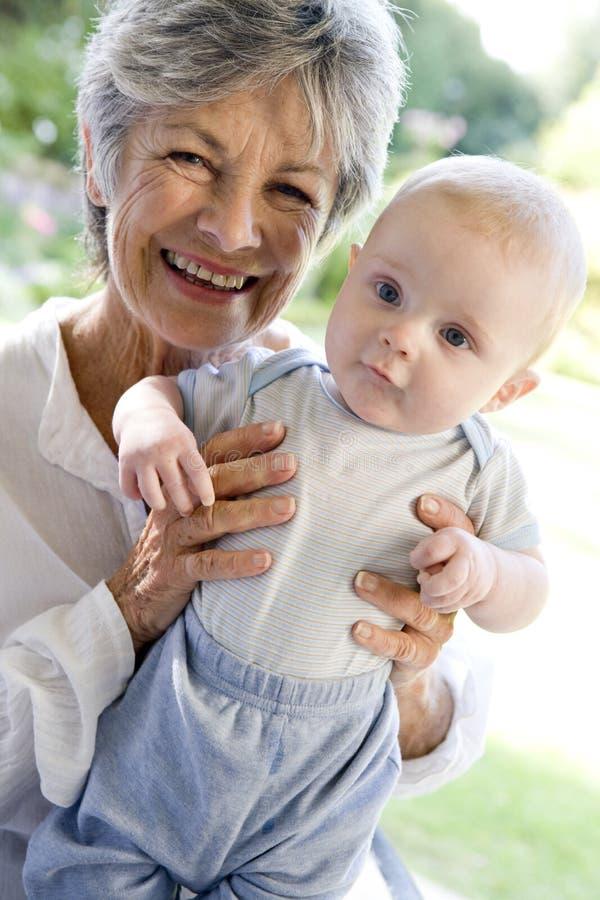 Abuela al aire libre en patio con el bebé fotografía de archivo libre de regalías