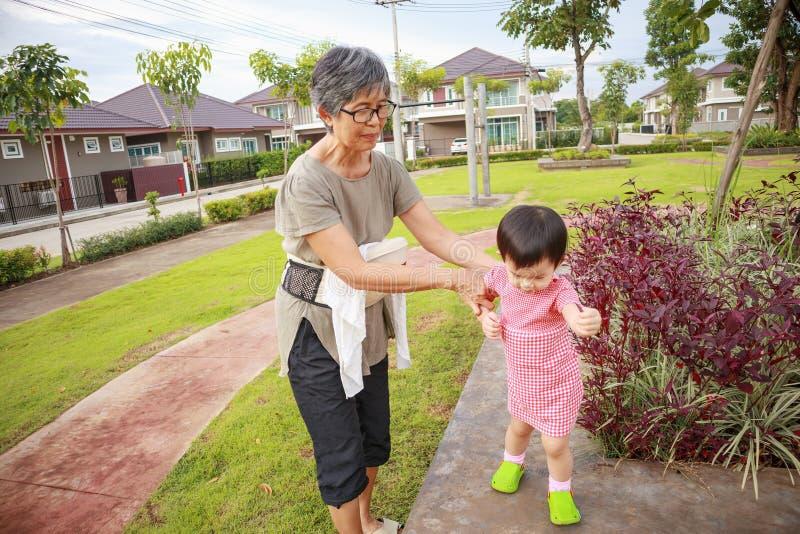 Abuela asiática con la nieta mientras que juega en el parque foto de archivo