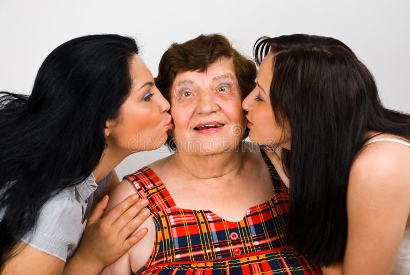 Abuela besada por dos nietas foto de archivo libre de regalías