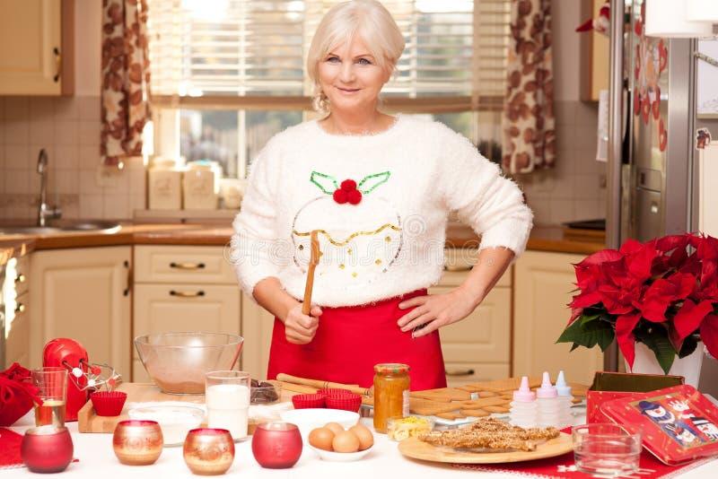 Abuela bonita en la cocina, tiempo de la Navidad fotos de archivo