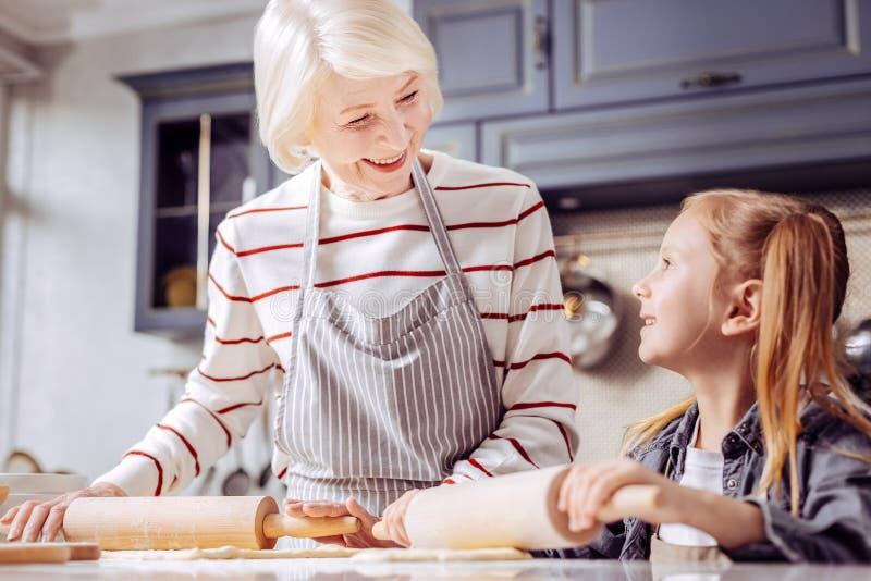 Abuela buena que sonríe mientras que cocina con su nieta bonita imagen de archivo