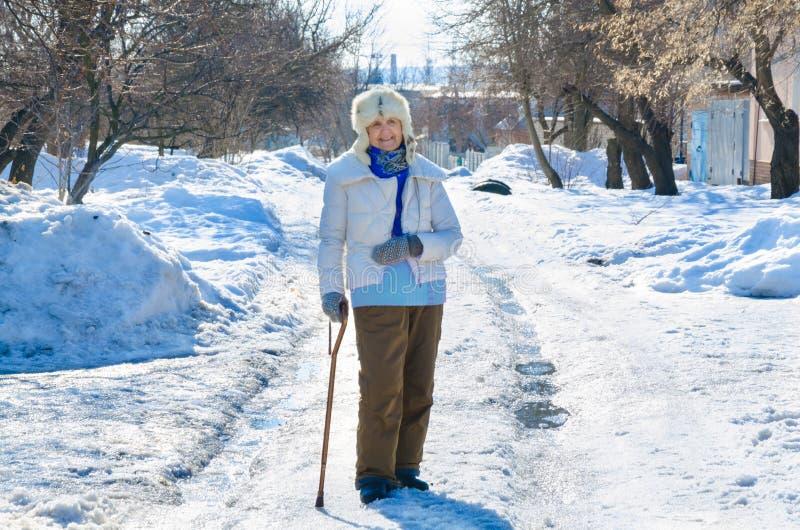 Abuela con el bastón en el camino en parque persona mayor que se inclina en un bastón mayor femenino caucásico en el invierno frí fotos de archivo libres de regalías