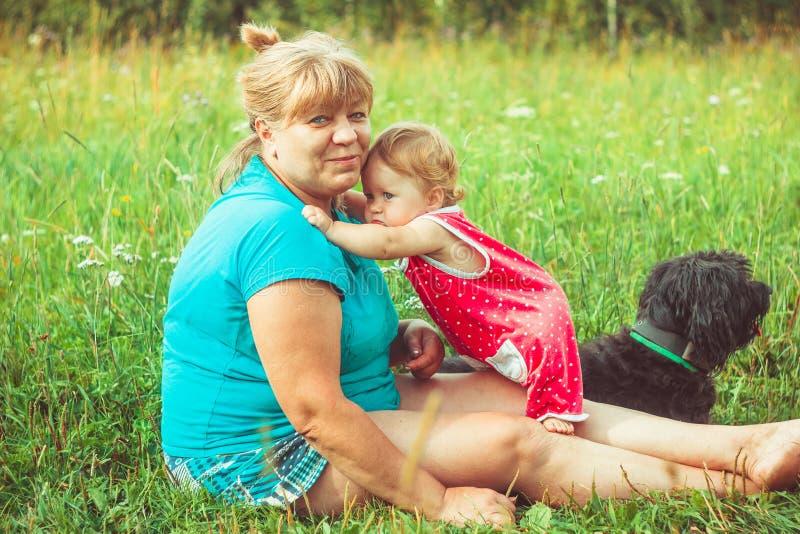 Abuela con la nieta en la hierba imagenes de archivo