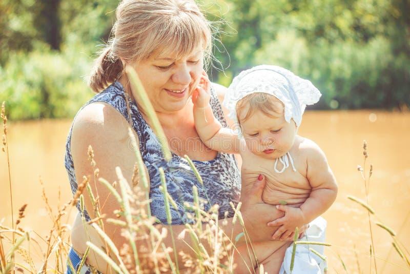 Abuela con la nieta en sus brazos fotografía de archivo libre de regalías