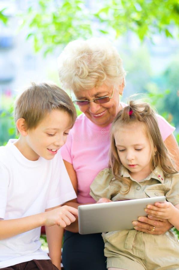Abuela con los nietos que usan la tableta foto de archivo libre de regalías