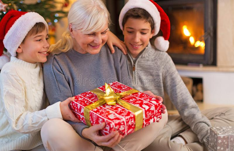 Abuela con sus dos nietos, sosteniendo un regalo de la Navidad fotografía de archivo libre de regalías