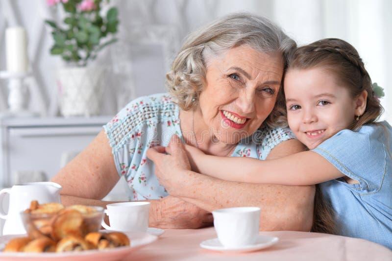 Abuela con un té de consumición de la pequeña nieta imágenes de archivo libres de regalías