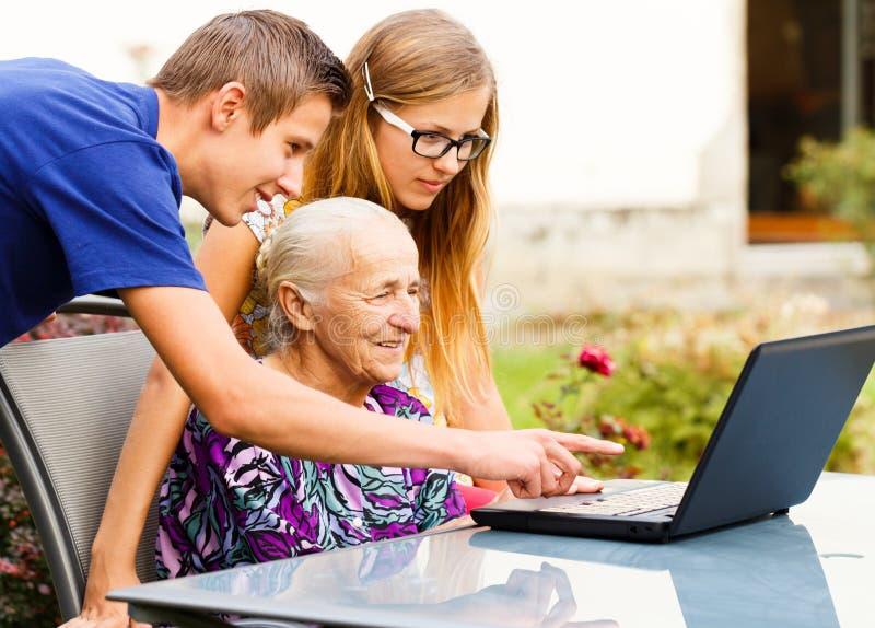 Abuela de ayuda del nieto con tecnología moderna imagenes de archivo