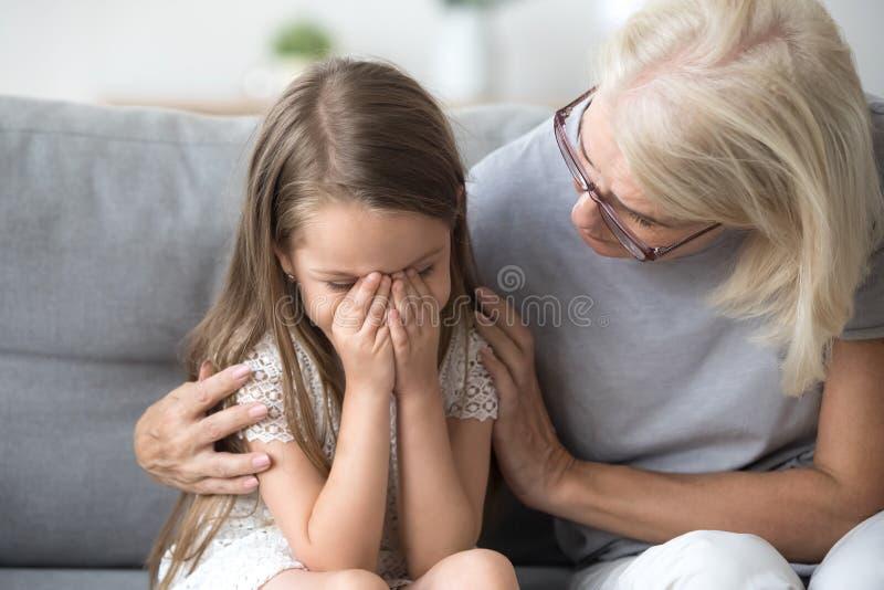 Abuela de comprensión de amor que abraza poco comfor gritador de la muchacha fotografía de archivo libre de regalías