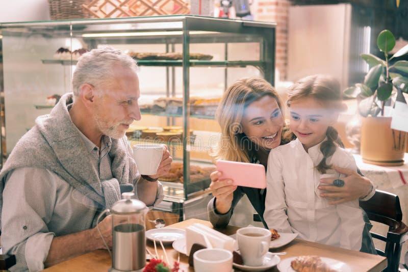 Abuela de emisión que muestra a su muchacha linda algunas fotos de familia imagen de archivo libre de regalías