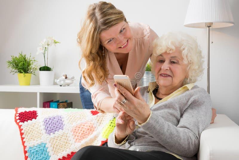 Abuela de enseñanza de la nieta cómo al teléfono celular usemodern foto de archivo libre de regalías