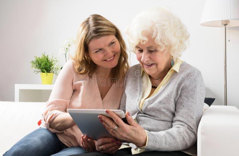 Abuela de enseñanza de la nieta cómo utilizar la tableta fotos de archivo