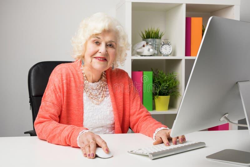 Abuela de trabajo en la oficina que se sienta por el ordenador imágenes de archivo libres de regalías