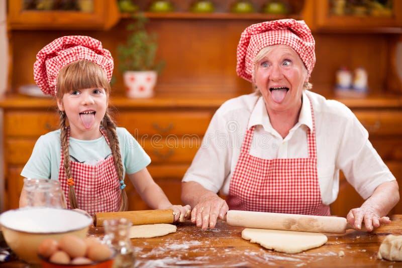 Abuela divertida y pequeño lollygag de la nieta en el kitch fotos de archivo