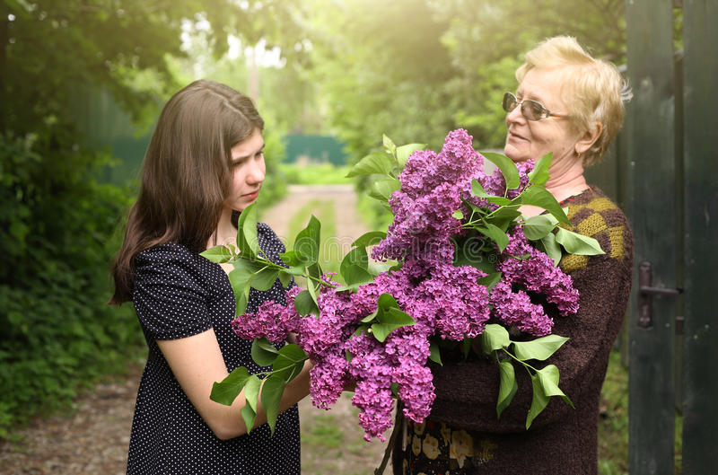 Abuela e hija magnífica con el ramo de la lila imagenes de archivo