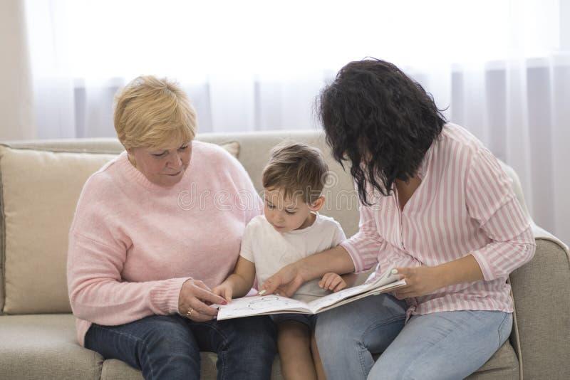Abuela e hija que leen un cuento a su nieto Ocio de lectura de la familia imagenes de archivo