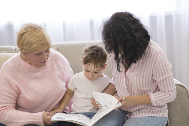 Abuela e hija que leen un cuento a su nieto Ocio de lectura de la familia fotos de archivo
