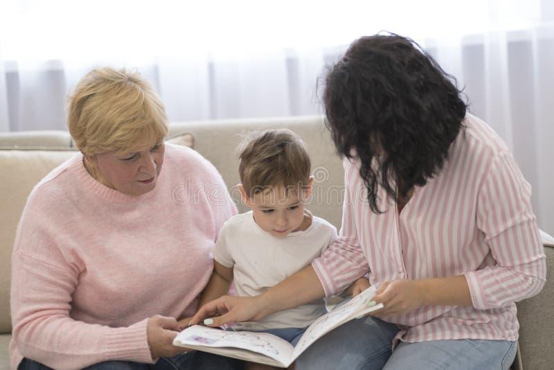 Abuela e hija que leen un cuento a su nieto Ocio de lectura de la familia fotografía de archivo libre de regalías