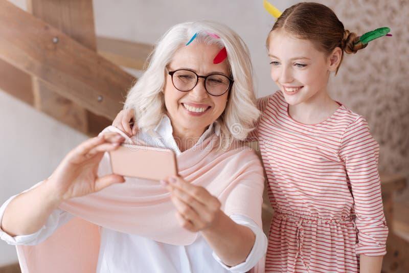 Abuela encantada y nieta positivas que toman una foto fotos de archivo libres de regalías