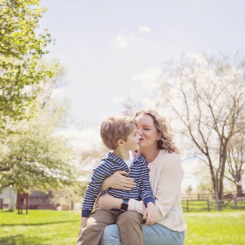 Abuela feliz que besa al nieto en parque imagenes de archivo