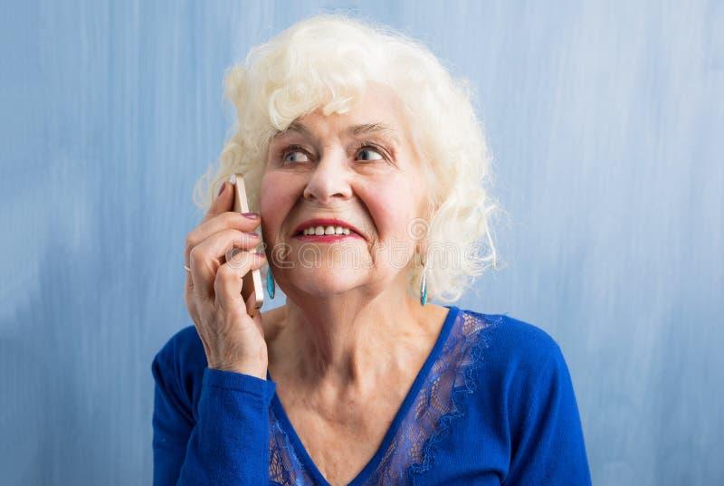Abuela feliz que habla en smartphone imagen de archivo