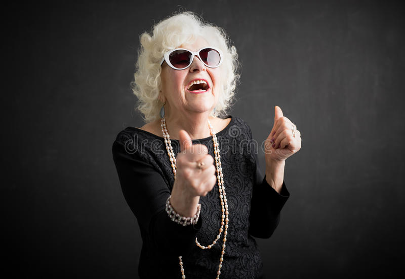 Abuela fresca con sus pulgares para arriba fotos de archivo